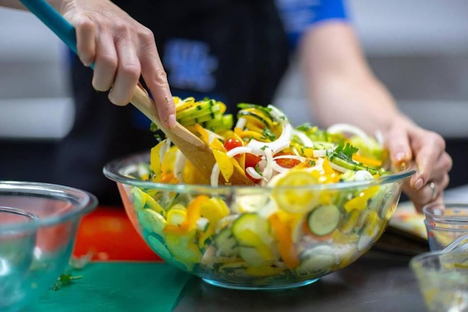 Woodford County Family & Consumer Sciences Extension Agent Elizabeth Coots prepares a garden patch salad, a mix of sliced summer vegetables tossed with a vinegar dressing July 7, 2021 in Versailles. Coots was making the dish as part of a livestream, preparing recipes from the University of Kentucky Cooperative Extension Service's food and nutrition calendar.