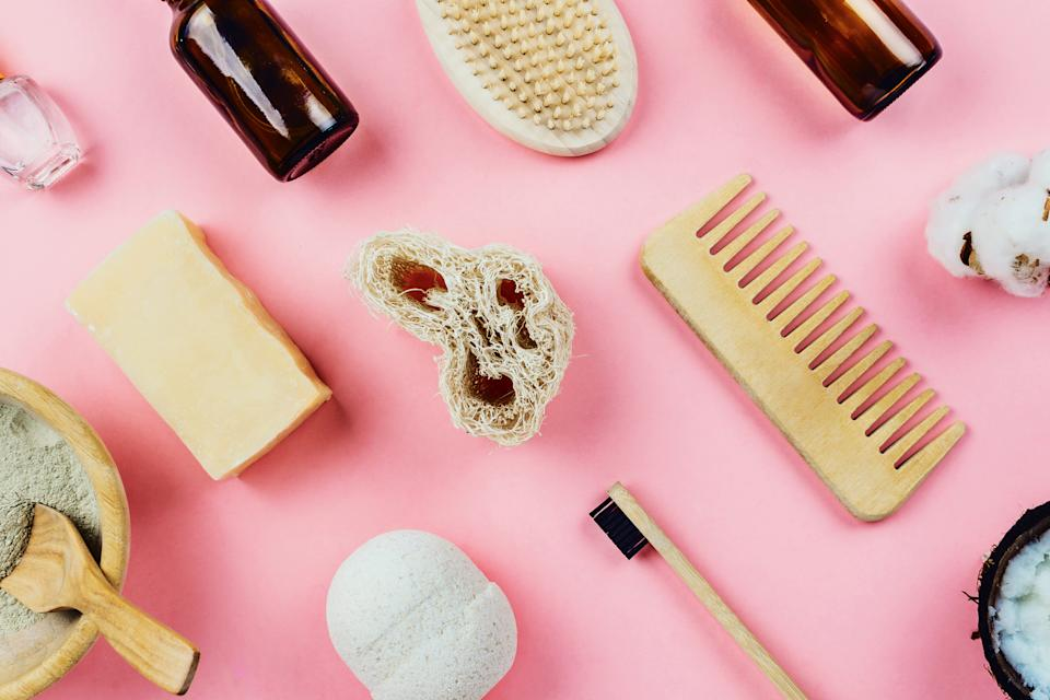 Flatlay of various beauty zero waste sustainable beauty and bath products on pink