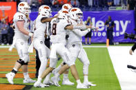 Oklahoma State players, led by quarterback Dru Brown, front, point at end zone camera as they celebrate a touchdown by Brown during the first half of the Texas Bowl NCAA college football game against Texas A&M on Friday, Dec. 27, 2019, in Houston. (AP Photo/Michael Wyke)