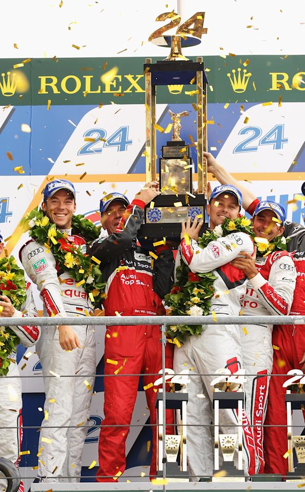 LE MANS, FRANCE - JUNE 17:  The winning car Audi Sport Team Joest R18 E-Tron Quattro (front right No.1) of Andre Lotterer, Marcel Fassler and Benoit Treluyer cross the finishing line at the end of the Le Mans 24 Hour race at the Circuit de la Sarthe on June 16, 2012 in Le Mans, France.  (Photo by Bryn Lennon/Getty Images)