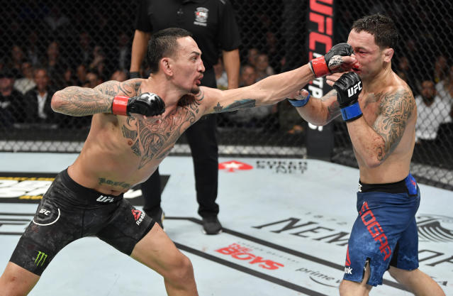 Max Holloway (L) punches Frankie Edgar in their UFC featherweight championship bout during UFC 240 at Rogers Place on Saturday. (Getty Images)