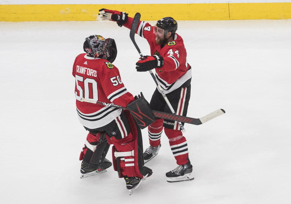 Chicago Blackhawks goalie Corey Crawford (50) and Calvin de Haan (44) celebrate their win over the Edmonton Oilers in an NHL hockey playoff game Friday, Aug. 7, 2020, in Edmonton, Alberta. (Jason Franson/Canadian Press via AP)
