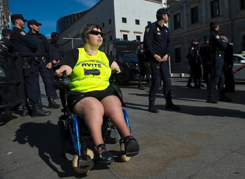 A disabled woman affected by phocomelia, malformation of the limbs, due to thalidomide drives a wheelchair during a protest in front of the Spanish parliament called by Avite, in Madrid, April 28, 2015