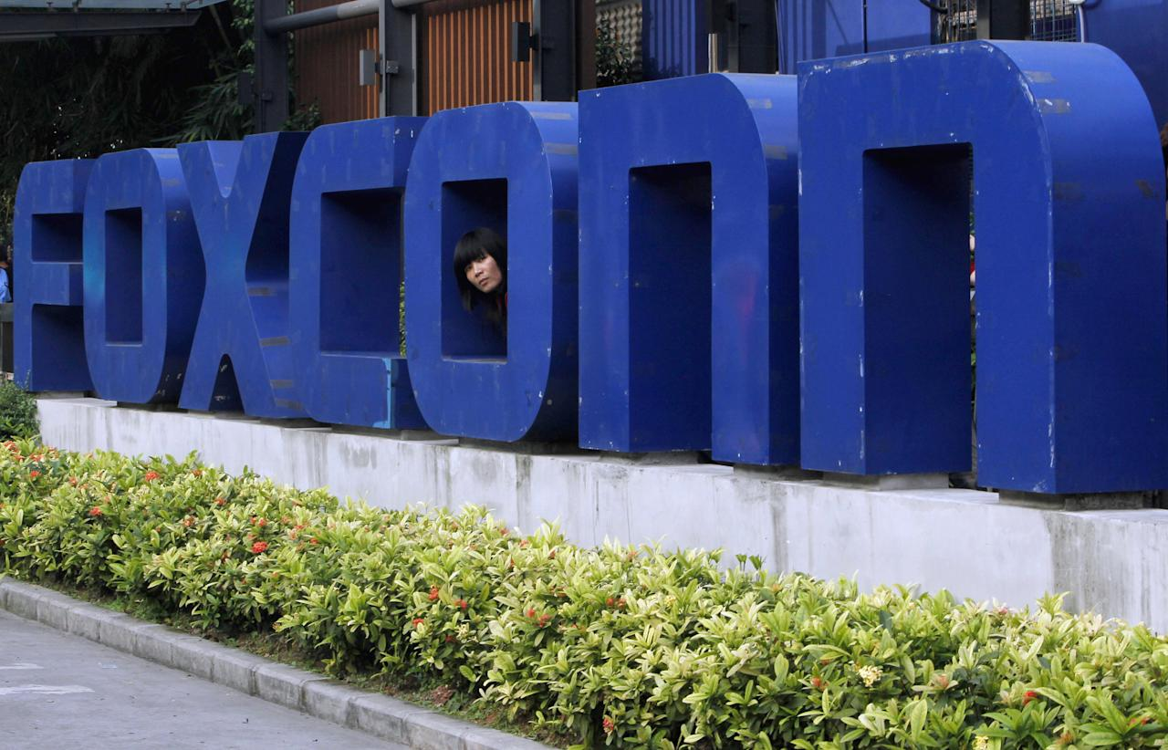FILE - In this May 27, 2010 file photo, a worker looks out through the logo at the entrance of the Foxconn complex in the southern Chinese city of Shenzhen. The Wisconsin Assembly plans to approve a $3 billion tax break bill for Taiwan-based Foxconn Technology Group to build a new display panel factory in the state. The incentive package up for a vote Thursday, Aug. 16, 2017, would be the largest in state history and the biggest to a foreign company in U.S. history. (AP Photo/Kin Cheung, File)