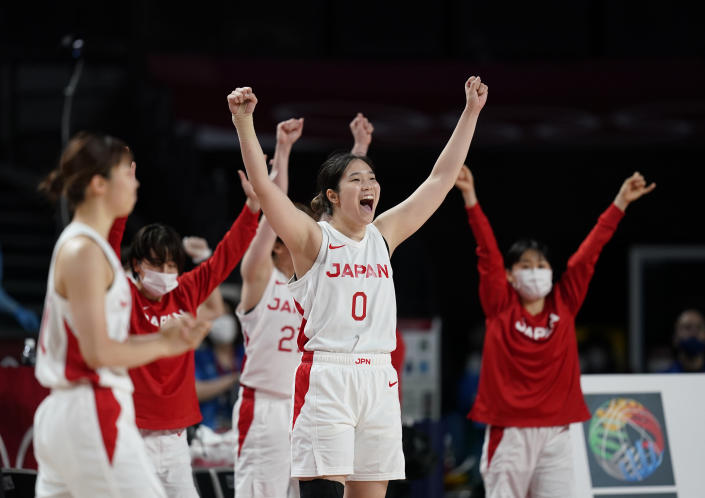 Japan players celebrate their win in the women's basketball preliminary round game against France at the 2020 Summer Olympics, Tuesday, July 27, 2021, in Saitama, Japan. (AP Photo/Charlie Neibergall)