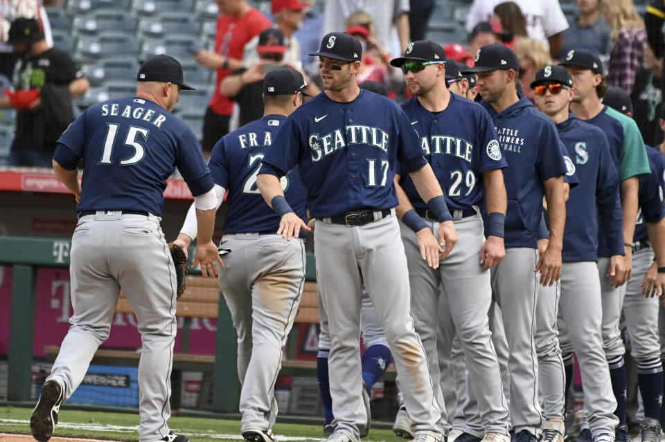 Seattle Mariners' Kyle Seager (15) is congratulated by Mitch Haniger (17) and teammates after beating the Los Angeles Angels 5-1, Sunday, Sept. 26, 2021, in Anaheim, Calif. (AP Photo/Michael Owen Baker)