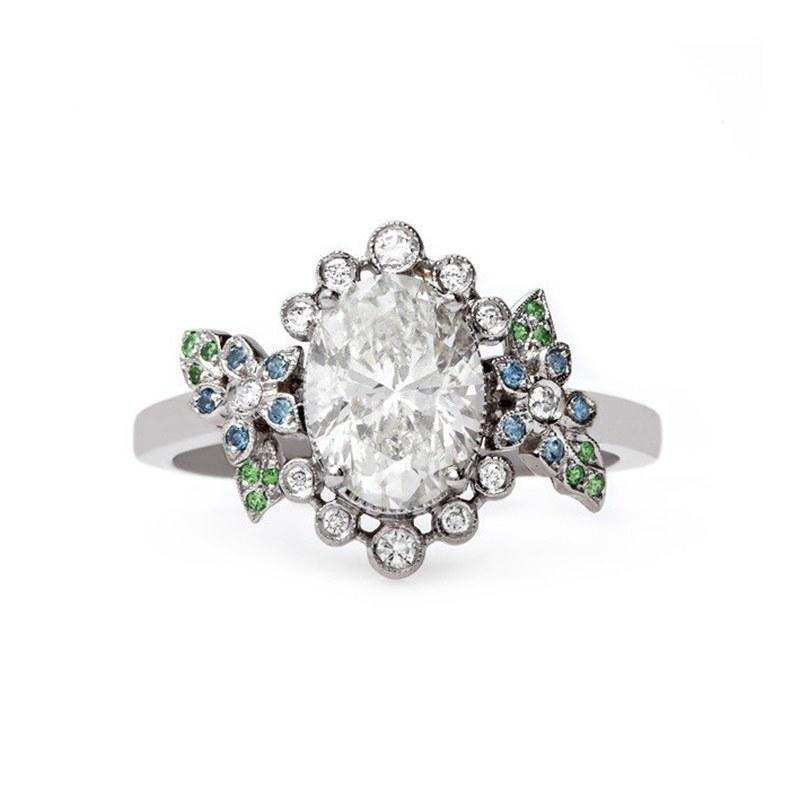 "Dreaming of a fairytale ring? Nature and eternal love are beautifully manifested in this whimsical design. Sapphire and tsavorite garnet flower petals adorn the sides for an ethereal effect. (""Thalia"" engagement ring, $15,950, Claire Pettibone Fine Jewelry Collection available at Trumpet & Horn)"