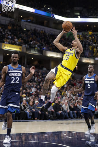 Indiana Pacers guard Jeremy Lamb (26) shoots between Minnesota Timberwolves forward Andrew Wiggins (22) and center Gorgui Dieng (5) during the second half of an NBA basketball game in Indianapolis, Friday, Jan. 17, 2020. The Pacers won 116-114. (AP Photo/Michael Conroy)