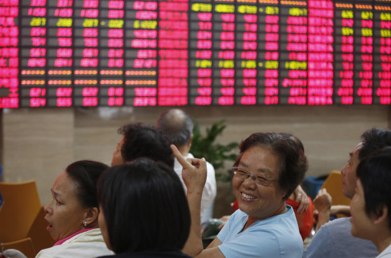 Investors chat each other at a private securities company Monday, Aug. 26, 2013 in Shanghai, China. Asian stock markets mostly rose Monday after expectations for an imminent phasing out of the Federal Reserve's monetary stimulus program began to fade. (AP Photo)