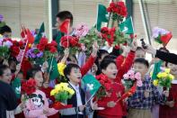 Children holding Chinese and Macau flags get ready before Chinese President Xi Jinping's arrival at Macau International Airport in Macau