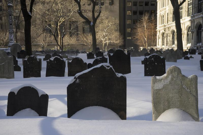 Snow lies over head stones at Trinity Church Cemetery during a winter storm in New York