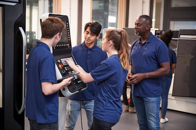 Apprentices being shown how to use a tool making machine. Photo: Getty