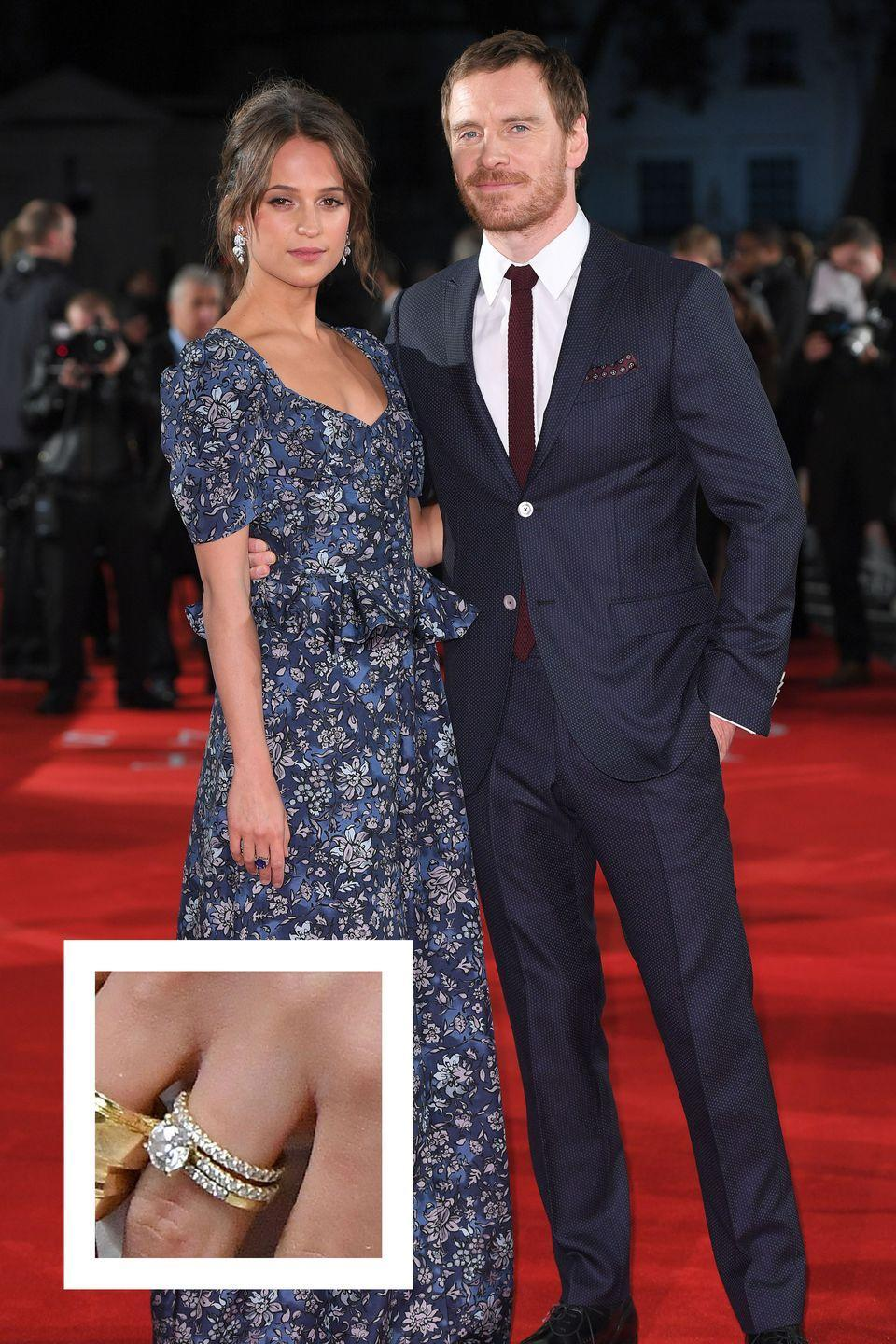 """<p>Vikander and Michael Fassbender wed in a secret ceremony in in Ibiza back in October 2017. A few weeks later, Vikander subtly debuted her engagement and wedding rings on the red carpet. Her ring is a solitaire diamond on a yellow gold pavé band with matching diamond eternity bands on each side, <a href=""""https://www.elle.com.au/celebrity/alicia-vikander-engagement-ring-14803"""" rel=""""nofollow noopener"""" target=""""_blank"""" data-ylk=""""slk:Elle Australia reports."""" class=""""link rapid-noclick-resp""""><em>Elle Australia </em>reports.</a></p>"""