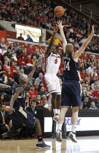 Rutgers guard Eli Carter (5) shoots against Notre Dame's Scott Martin (14) and Jerian Grant during the second half of an NCAA college basketball game, Monday, Jan. 16, 2012, in Piscataway, N.J. Rutgers won 65-58. (AP Photo/Julio Cortez)