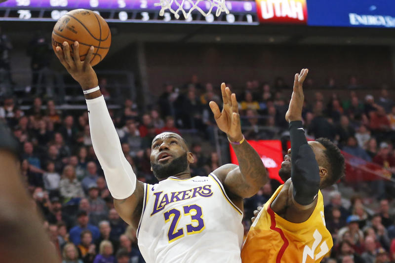 Utah Jazz forward Jeff Green, right, defends against Los Angeles Lakers forward LeBron James, left, as he drives to the basket in the first half during an NBA basketball game Wednesday, Dec. 4, 2019, in Salt Lake City. (AP Photo/Rick Bowmer)