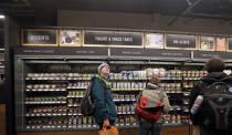 FILE - In this Jan. 22, 2018, file photo, a customer looks overhead in an Amazon Go store, where sensors and cameras are part of a system used to tell what people have purchased and charge their Amazon account in Seattle. A small number of restaurants and stores are going cash-free in the U.S., looking to cater to customers who increasingly pay with a card or smartphone. But a backlash is growing against the practice that some say discriminates against those who lack back accounts or rely on cash for most of their daily transactions. (AP Photo/Elaine Thompson, File)