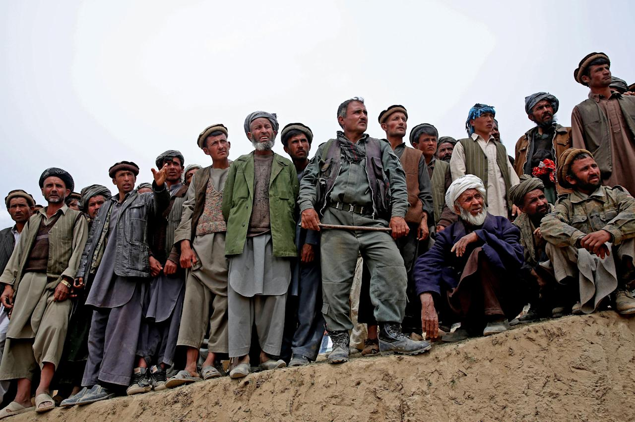 In this Sunday, May 4, 2014 photo, Survivors line up to receive donations near the site of Friday's landslide that buried Abi-Barik village in Badakhshan province, northeastern Afghanistan. The landslide Friday killed hundreds of people — still no one has an exact number — and destroyed 300 homes and displaced hundreds more families. (AP Photo/Massoud Hossaini)