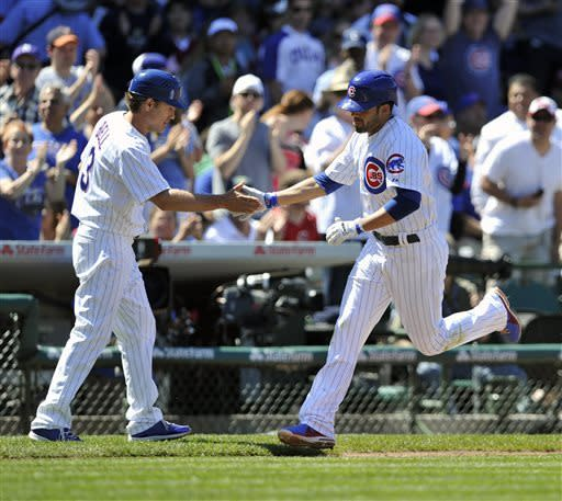 Chicago Cubs' David Bell left, congratulates David DeJesus as he rounds third after hitting a solo home run against the Cincinnati Reds in the fifth inning of a baseball game Thursday, June 13, 2013, in Chicago. (AP Photo/Jim Prisching)