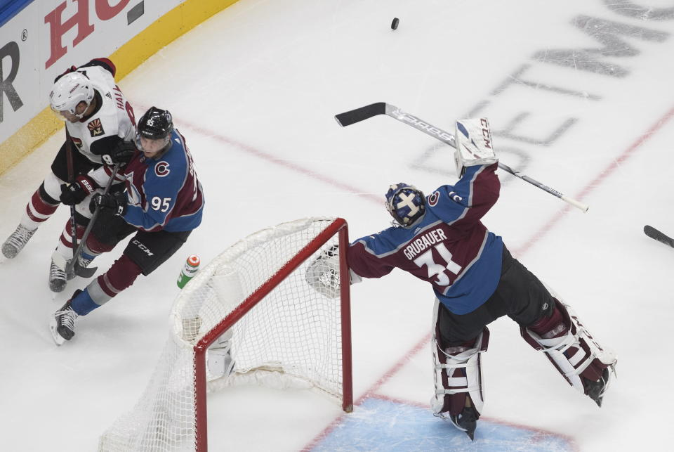 Arizona Coyotes' Taylor Hall (91) and Colorado Avalanche' Andre Burakovsky (95) look for the rebound from goalie Philipp Grubauer (31) during the second period of a first round NHL Stanley Cup playoff hockey series in Edmonton, Alberta, Friday, Aug. 14, 2020. (Jason Franson/The Canadian Press via AP)