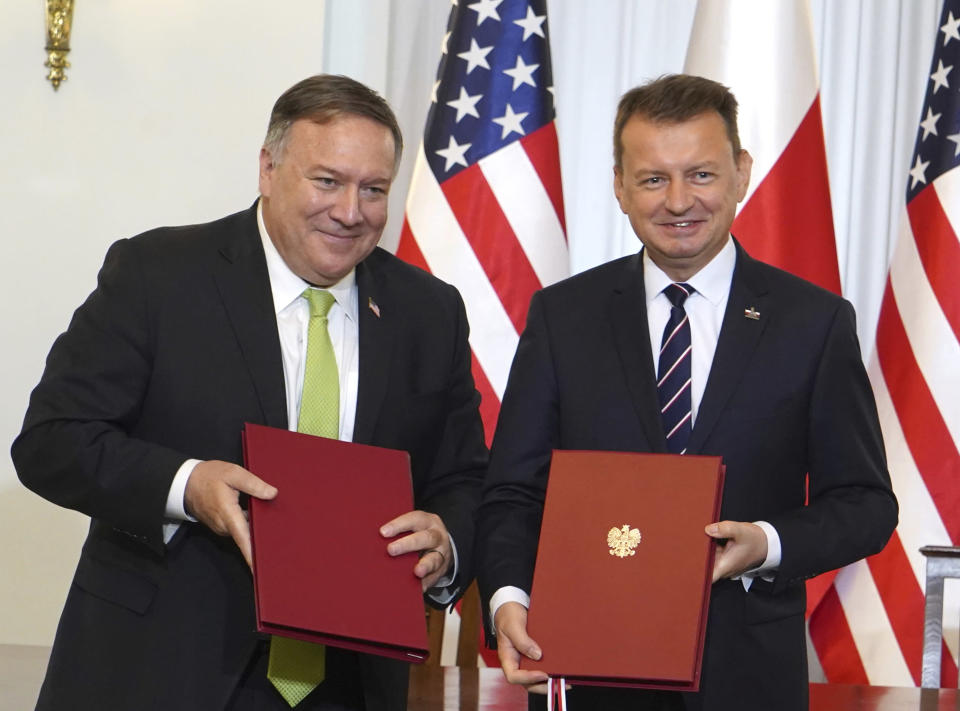 US Secretary of State Mike Pompeo, left, and Poland's Minister of Defence Mariusz Blaszczak pose for the media after signing the US-Poland Enhanced Defence Cooperation Agreement in the Presidential Palace in Warsaw, Poland, Saturday Aug. 15, 2020. Pompeo is on a five day visit to central Europe. (Janek Skarzynski/Pool via AP)