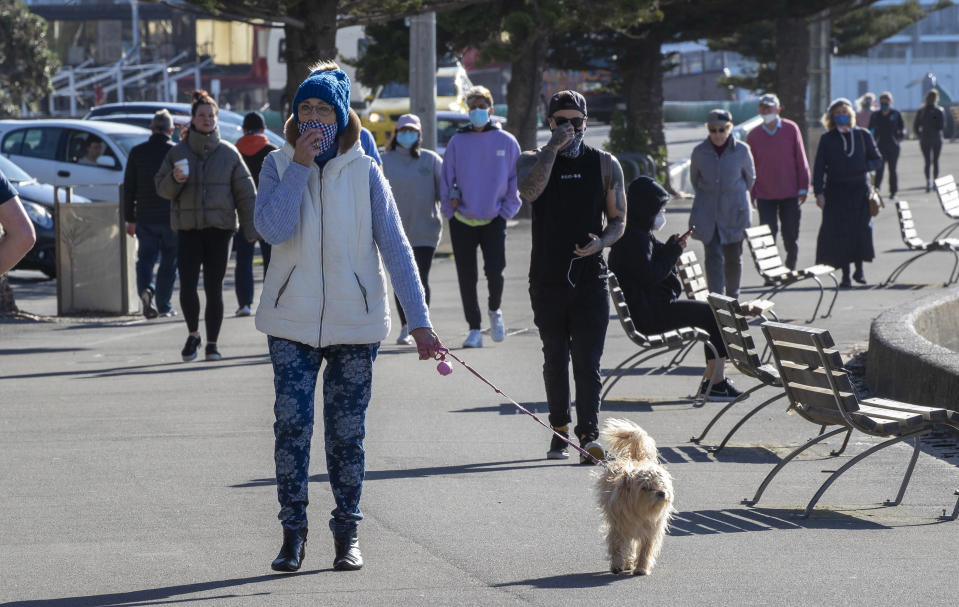 People, some wearing masks, walk along a path in Wellington, New Zealand Thursday, Aug. 19, 2021. Japan, Australia and New Zealand all got through the first year of the coronavirus pandemic in relatively good shape, but now are taking diverging paths in dealing with new outbreaks of the fast-spreading delta variant. (Mark Mitchell/New Zealand Herald via AP)