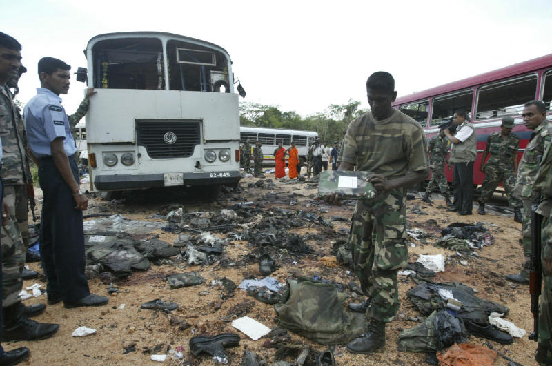 FILE - In this Oct. 16, 2006, file photo, a Sri Lankan soldier inspects the debris at the site of a suicide explosion by Tamil Tigers near Dambulla, about 150 kilometers (90 miles) northeast of Colombo, Sri Lanka. The April 21, 2019 deadly Easter attacks in Sri Lanka are a bloody echo of decades past in the South Asian island nation, when militants inspired by attacks in the Lebanese civil war helped develop the suicide bomb vest. Over nearly 30 years of civil war, the Tamil Tigers would launch more than 130 suicide bomb attacks, making them the leading militant group in such assaults at the time. (AP Photo/Eranga Jayawardena, File)