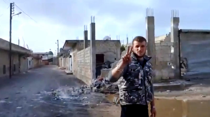 In this image taken from video obtained from the Ugarit News, which has been authenticated based on its contents and other AP reporting, A Free Syrian Army soldier flashes the victory sign, as damages caused by barrels fired from warplanes and rocket launchers is seen at background in Hama, Syria, on Monday, Jan. 28, 2013. (AP Photo/Ugarit News via AP video)