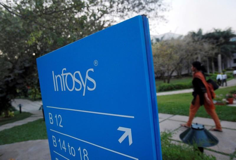FILE PHOTO: An employee walks past a signage board in the Infosys campus at the Electronics City IT district in Bangalore