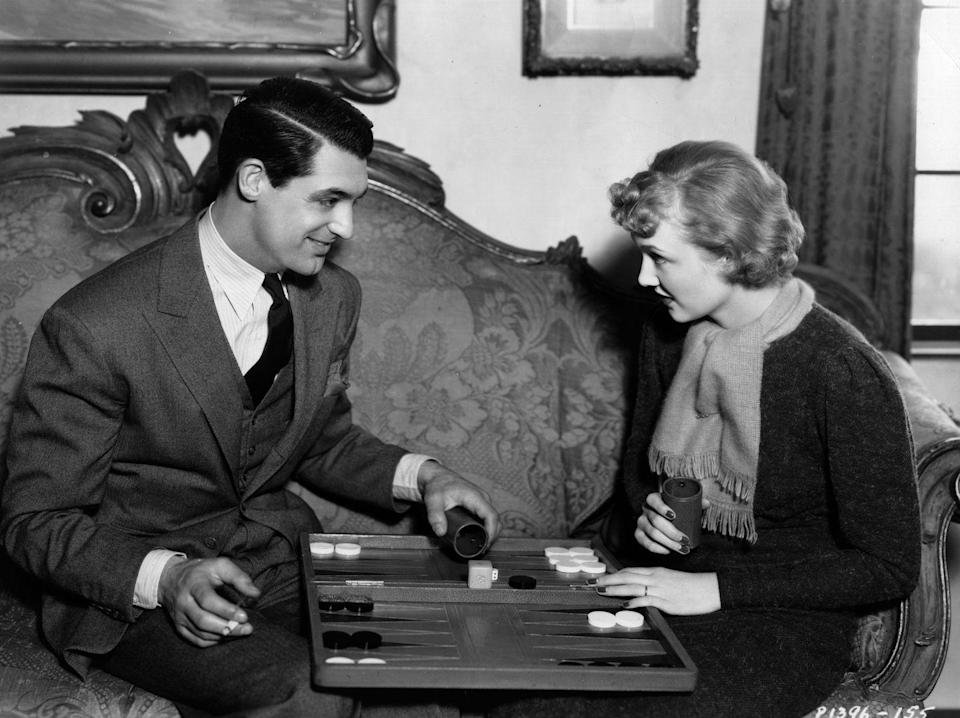 <p>Cary Grant and his first wife, actress Virginia Cherill, challenge each to a game of backgammon in their living room. </p>