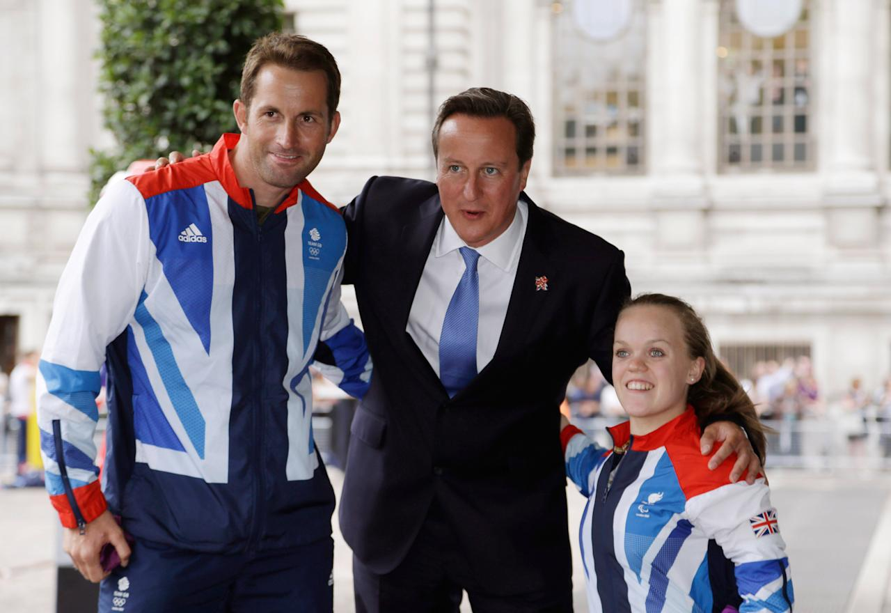 LONDON, UNITED KINGDOM - SEPTEMBER 10:   British Prime Minister David Cameron poses with Team GB gold medallist sailor Ben Ainslie (L) and Paralympics GB gold medallist swimmer Ellie Simmonds (R) before hosting a reception for Team GB and Paralympic GB athletes on September 10, 2012 in London, England. Thousands of people waving British flags lined the streets of London earlier on Monday for the London 2012 Victory Parade for Team GB and Paralympic GB athletes, to toast the athletes behind the country's unprecedented summer of sporting success.  (Photo by  Lefteris Pitarakis - WPA Pool/Getty Images)