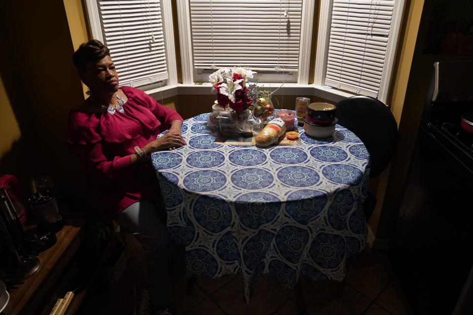 Karla Jefferies sits in her kitchen in Detroit, Friday, March 5, 2021. Jefferies, 64, a retired state worker in Detroit, Michigan, tested positive for COVID-19 in March 2020 and has been bothered by puzzling symptoms ever since. First it was fatigue, fever, and no taste or smell. Then came brain fog, insomnia, a nagging smell of something burning that only recently disappeared, and intermittent ringing in her ears. Now she can't hear out of her left ear. (AP Photo/Paul Sancya)