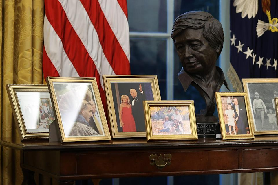 Abronze bust ofMexican-American labor leaderCésar Chávez overlooks photographs on a table behind the Resolute Desk in the Oval Office while President Joe Biden prepares to sign a series of executive orders just hours after his inauguration on Jan. 20, 2021, in Washington, D.C.