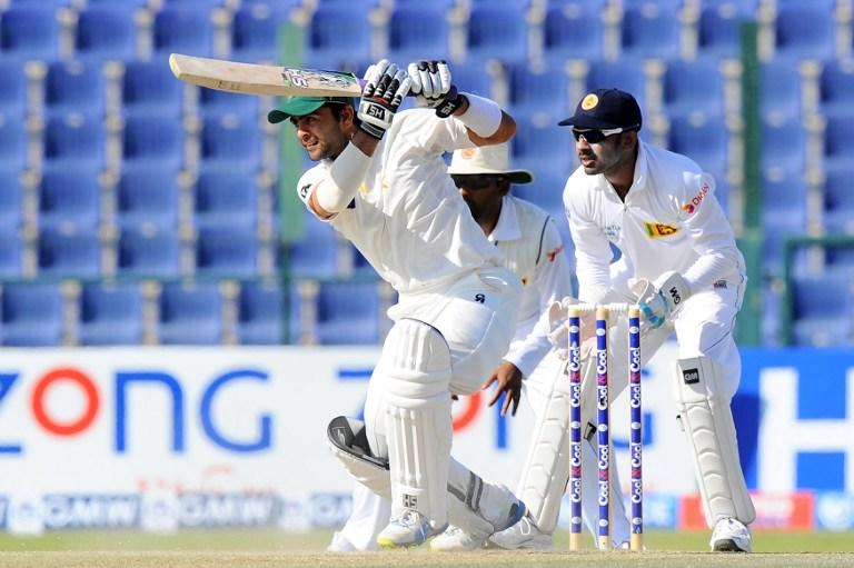 Pakistan batsman Ahmed Shehzad (L) plays a shot as Sri Lankan wicketkeeper Prasanna Jayawardene (R) looks on during the final day of the first cricket Test match between Pakistan and Sri Lanka at the Sheikh Zayed Stadium in Abu Dhabi on January 4, 2014. AFP PHOTO/Ishara S. KODIKARA