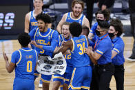 UCLA players celebrate after beating Alabama 88-78 in overtime of a Sweet 16 game in the NCAA men's college basketball tournament at Hinkle Fieldhouse in Indianapolis, Sunday, March 28, 2021. (AP Photo/AJ Mast)