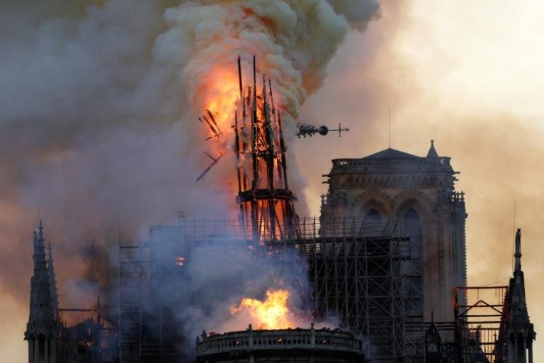 The steeple and spire collapses as smoke and flames engulf the Notre-Dame cathedral