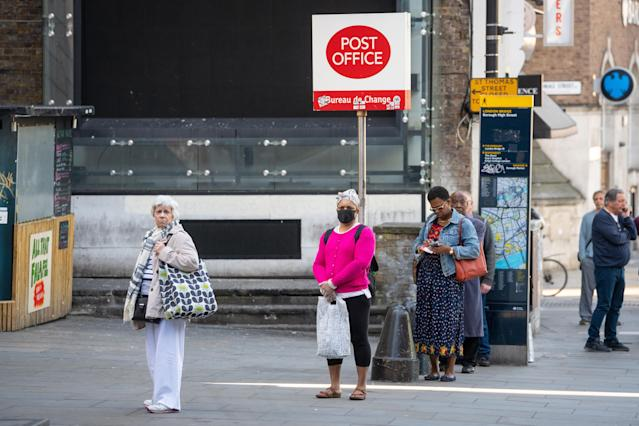 People queue for a branch of the Post Office near London Bridge, London, after the introduction of measures to bring the country out of lockdown. (Photo by Dominic Lipinski/PA Images via Getty Images)