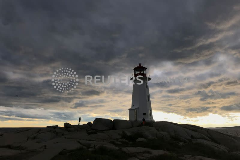 People walk on the rocks at the lighthouse at dusk in Peggy's Cov