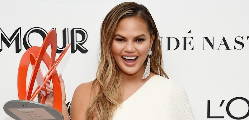 Chrissy Teigen grins while holding an award, wearing an off-the-shoulder white dress.