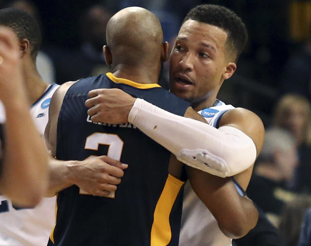 West Virginia's Jevon Carter, left, embraces Villanova's Jalen Brunson after an NCAA men's college basketball tournament regional semifinal Friday, March 23, 2018, in Boston. (AP Photo/Mary Schwalm)