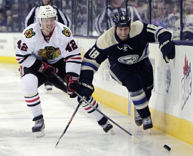 Chicago Blackhawks' Joakim Nordstrom, left, of Sweden, and Columbus Blue Jackets' RJ Umberger chase a loose puck during the second period of an NHL hockey game on Friday, April 4, 2014, in Columbus, Ohio. (AP Photo/Jay LaPrete)