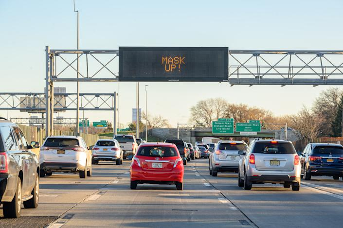 """A traffic sign reads, """"Mask up!"""" above a road in Westchester as the city continues the re-opening efforts following restrictions imposed to slow the spread of coronavirus on December 06, 2020 in New York City. (Noam Galai/Getty Images)"""