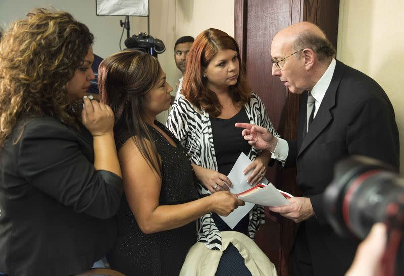Kenneth Feinberg, a victims compensation lawyer hired by GM, speaks with family members of GM crash victims, in Washington