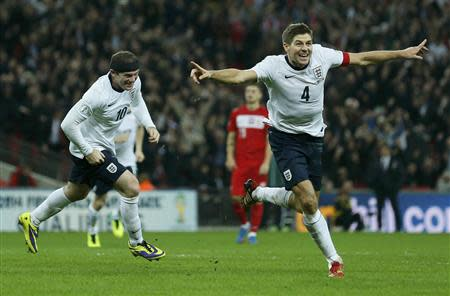 England captain Steven Gerrard (R) celebrates his goal with teammate Wayne Rooney during their 2014 World Cup qualifying soccer match against Poland at Wembley Stadium in London October 15, 2013. REUTERS/Stefan Wermuth