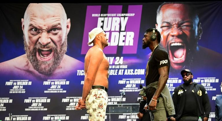 England's Tyson Fury, left, and American Deontay Wilder face off at a June news conference to promote their heavyweight title showdown, which has been moved to October 9 after Fury contracted Covid-19 (AFP/Frederic J. BROWN)