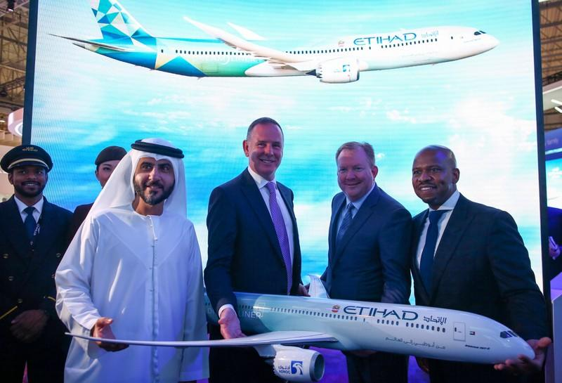 Etihad COO Mohammad Al-Bulooki, Etihad CEO Tony Douglas, Boeing Commercial Airplanes president, CEO Stanley A. Deal and Boeing Global Services President and CEO Ted Colbert pose for a photo in front of a Boeing 787 Dreamliner model at Dubai Air show, Dubai