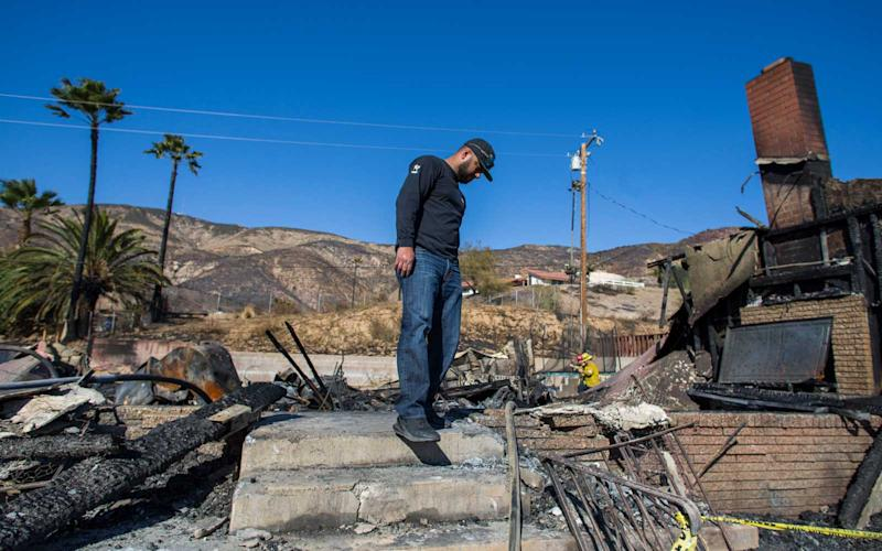 Matthew Valdivia,looks for personal objects among the ashes of his home at Viento Way after being burned out by the Hillside fire in San Bernardino, California on October 31, 2019. | APU GOMES/Getty Images