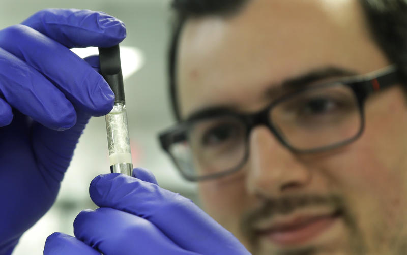 Pierce Prozy examines a Yolo! brand CBD vape oil cartridge at Flora Research Laboratories in Grants Pass, Ore., on July 19, 2019. The Associated Press commissioned the lab to test vape products marketed as delivering the cannabis extract CBD. AP chose samples by targeting brands that law enforcement authorities or users flagged as suspect. Ten of the 30 samples contained synthetic marijuana, a dangerous street drug commonly known as K2 or spice. (AP Photo/Ted Warren)