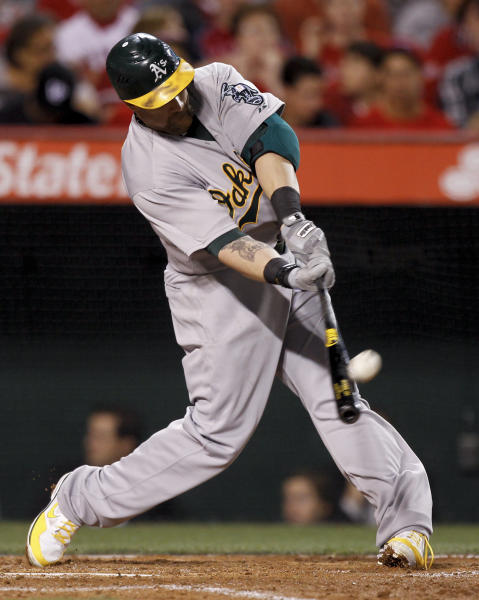 Oakland Athletics' Jonny Gomes hits a home run against the Los Angeles Angels during the sixth inning of a baseball game in Anaheim, Calif., Wednesday, April 18, 2012. (AP Photo/Chris Carlson)