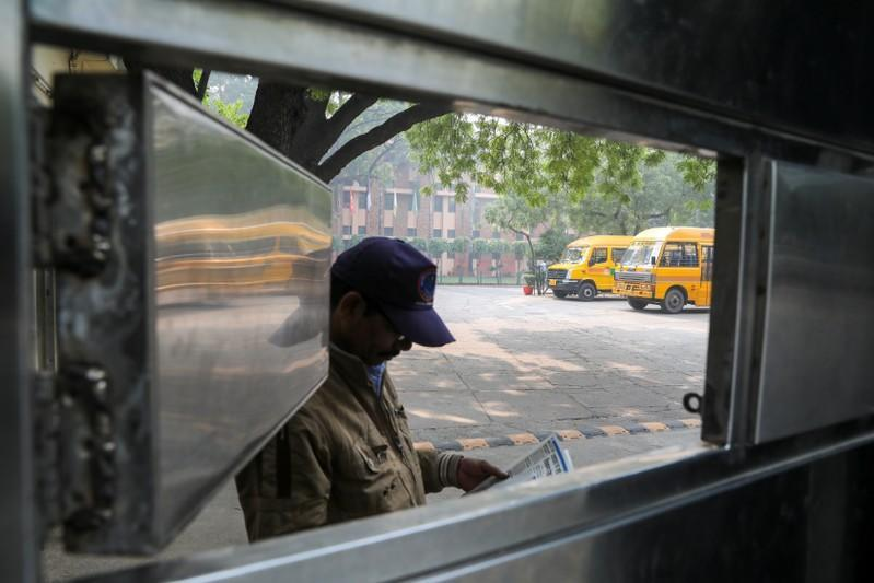 A security guard reads a newspaper inside the premises of a school which was shut because of smog in New Delhi