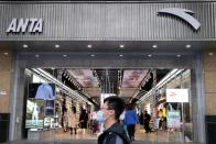 Man walks past an Anta Sports store at a shopping mall in Beijing